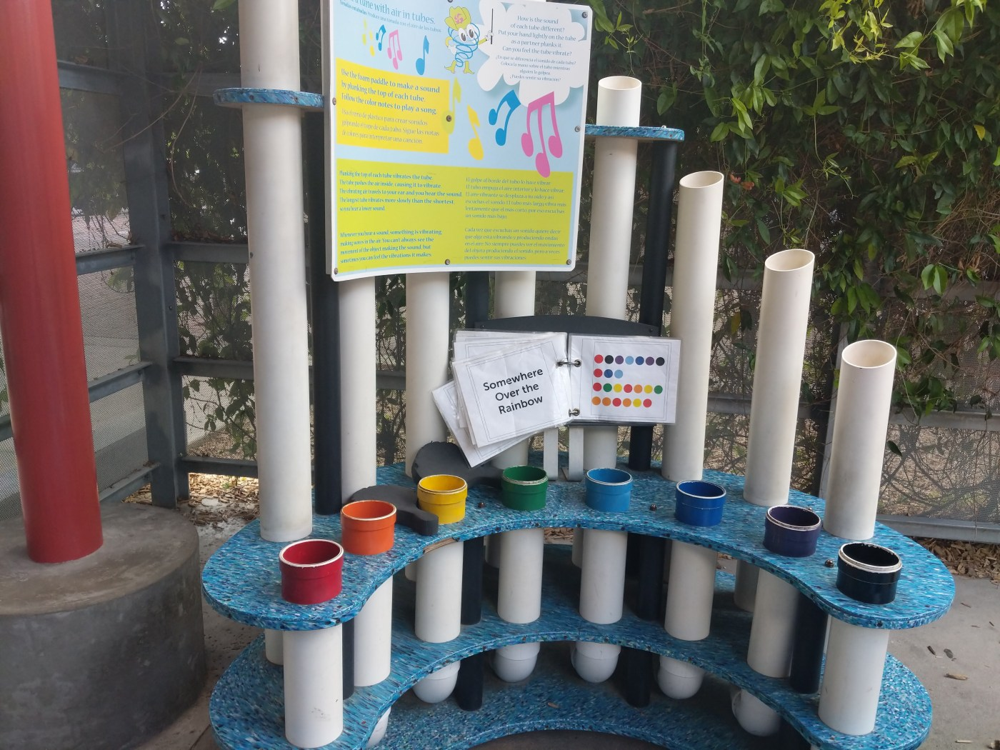 A series of different colored pipes on a structure with a mallet that can be hit to play music