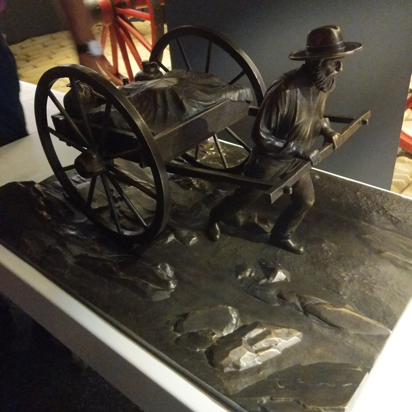 a bronze statue of a Mormon pioneer pushing a handcas