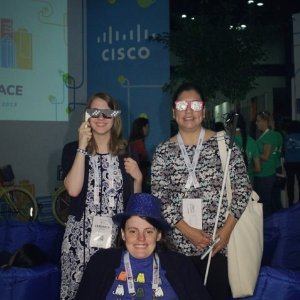 Veronica, Maria, and Liz smiling at a Cisco photo booth and wearing funny glasses