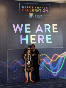 "Veronica and her human guide under a sign that says ""We are here, Grace Hopper Conference 2018"""