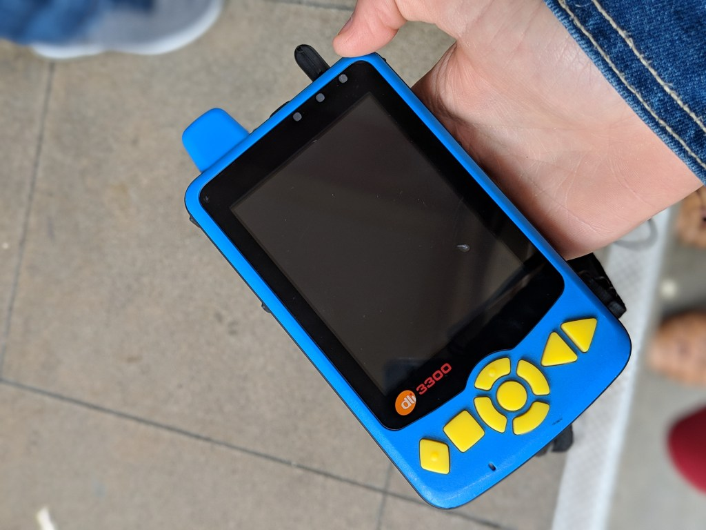 Veronica holding the blue and yellow audio description device in her hand. It is about the size of a cell phone and has a large screen with yellow buttons on the side