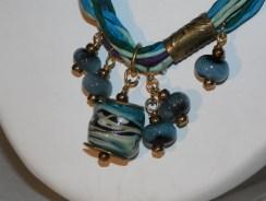 détail du collier soir, métal gravé et verre