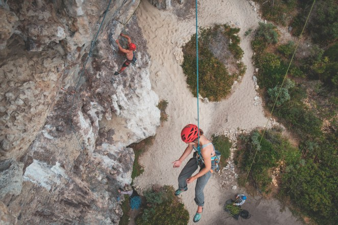 people-in-helmets-with-ropes-climbing-on-rocky-mountains-7084330