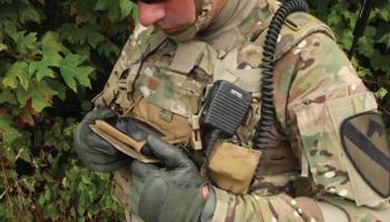 Солдат в форме США смотрит в экран смартфона