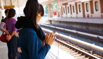 Девушка стоит на ж\д платформе и смотрит в свой смартфон