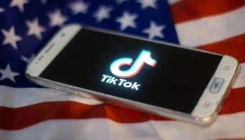 На флаге США лежит смартфон, на котором видно логотип ТикТок