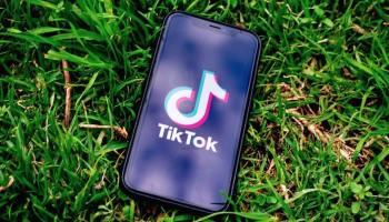 Телефон с логотипом ТикТок лежит на траве