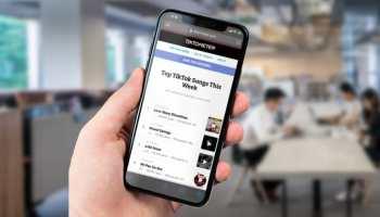 Рука держит смартфон, на экране которого виден сайт Тиктометр