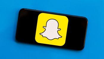 Лого Снепчата на смартфоне, который лежит на синем фоне