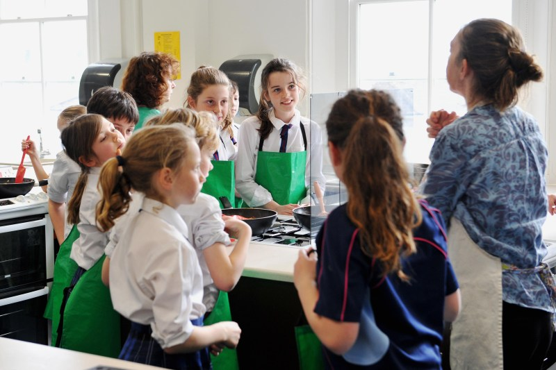 A teacher talks to her students in a college about home economics