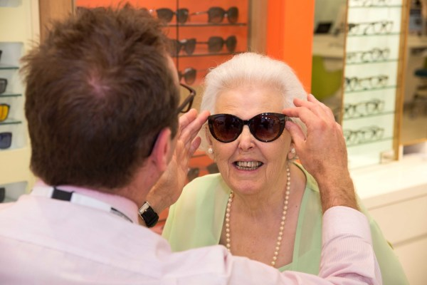 Photo by Liz Finlayson/Vervate Lisken Jellings (crrt) visits Vision Express in Brighton's Churchill Square ahead of Macular Awareness Week. Lisken is partially sighted and has Age Related Macular Degeneration (AMD). Lisken is pictured with store manager Simon Pike trying on some Solaris sunglasses For further info contact Kelly Hill at The Tonic Comms 0115 8532198