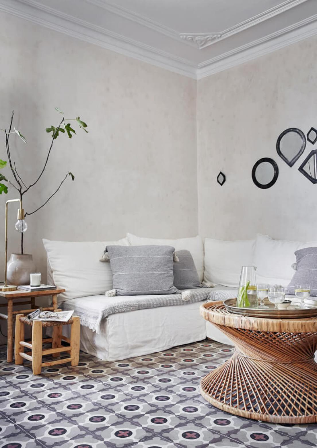 An inviting couch occupies one corner of the living and dining room the floor tiles are original fixtures while the interior walls have been plastered but