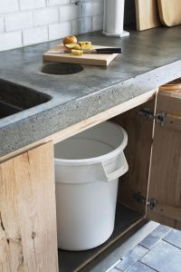 compost bin in concrete counter with trash can below