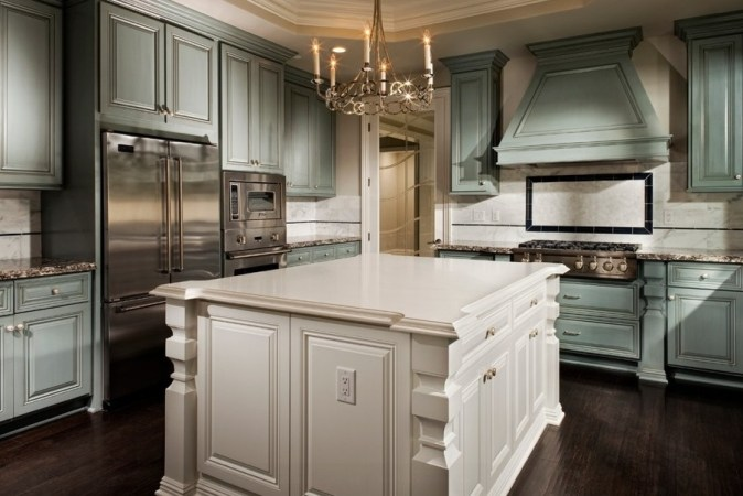 Traditional kitchens will always be in style. They work well in larger homes with a lot of architectural detail. This two-toned painted traditional kitchen has dark wood floors in keeping with the details of this look.