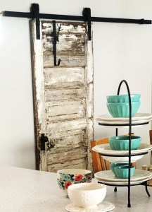 antique door hung on matte black barn door hardware
