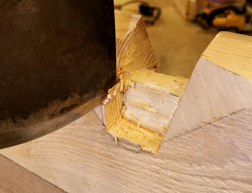 nærbilde av lafteteknikk, øks som skjærer ut laftespor
