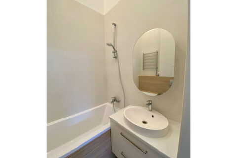 white bathroom with oval mirror