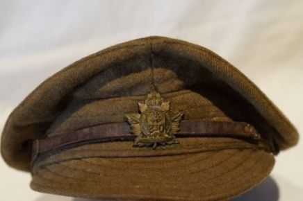 This hat differs from the peak cap in that the top is slouched down over the sides and the bill is soft and stitched like a baseball cap. The 230th Canadian Forestry Corps device is centered over the leather chinstrap (eBay image).