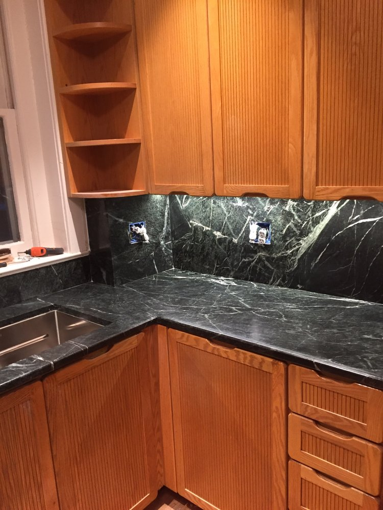 wooden cabinetry with black and white marble counter