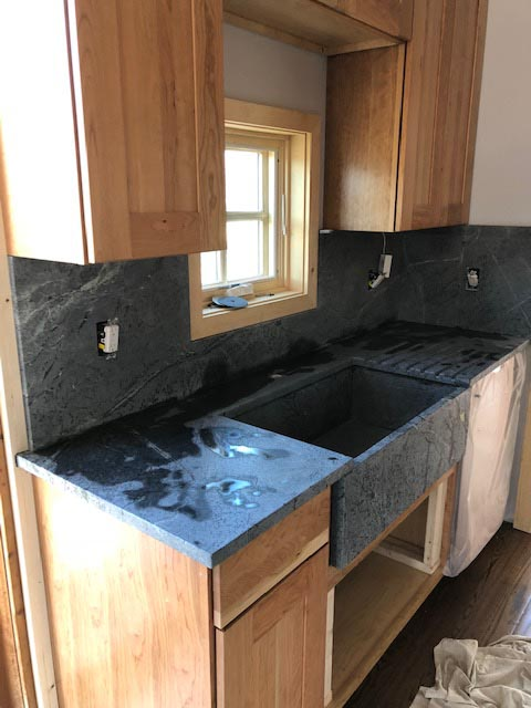 Installing a black counter top with wooden cupboards
