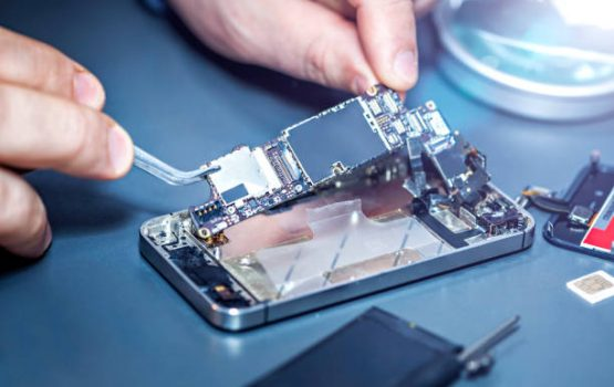 Technician repairs the damaged mobile phone. Serviceman is repairing a damaged cell phone. Technician repairs the damaged smartphone. Replacing the smartphone's motherboard.