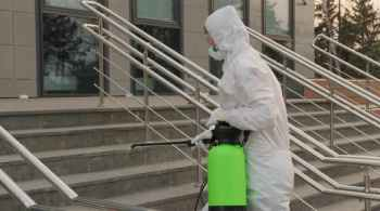 Worker In A Protective Suit Disinfects Surfaces From Coronavirus. Antibacterial Sanitary Measures On