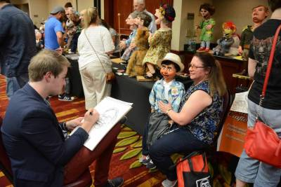 Austin Phillips drawing caricatures at his table