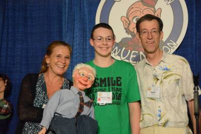 Lynn Trefzger and Gary Owen present a puppet to Christian Marks