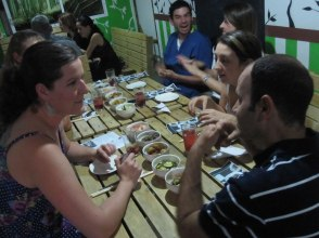 Invitados disfrutando el ambiente con platos de banchan. Guests enjoying the ambience while sharing banchan.