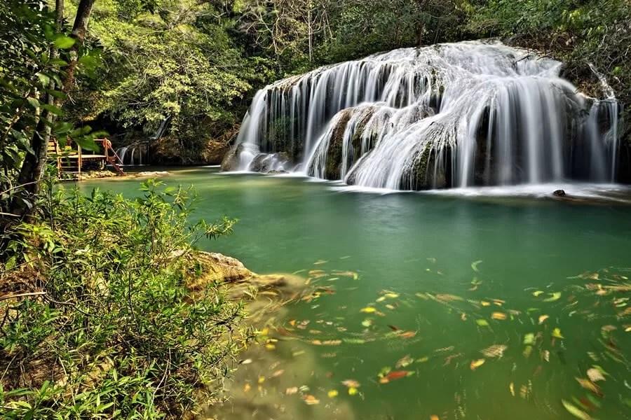 cachoeira em Bonito e água do rio esverdeada com folhas na superfície