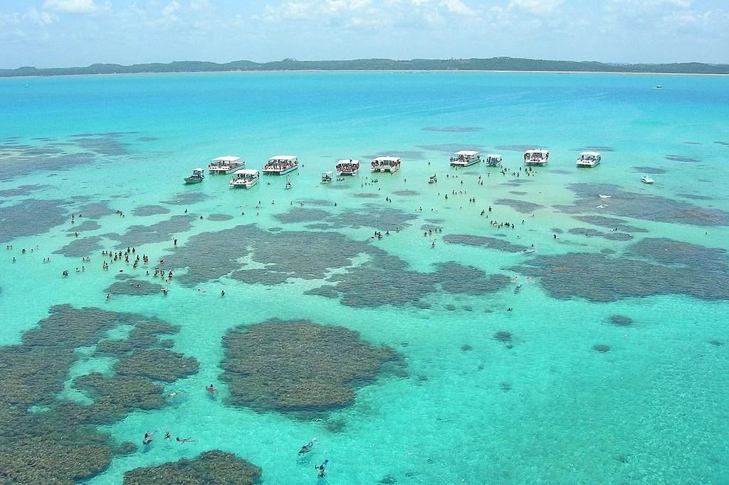 corais, banhistas e barcos nas piscinas naturais de Maragogi