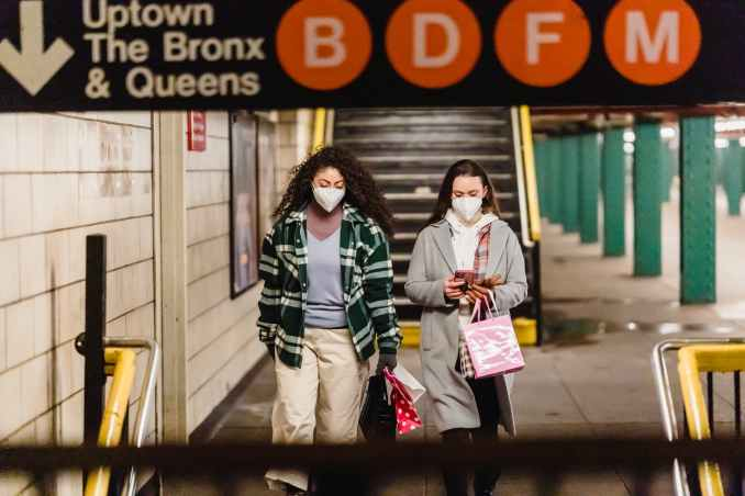 female friends walking in underground passage after shopping