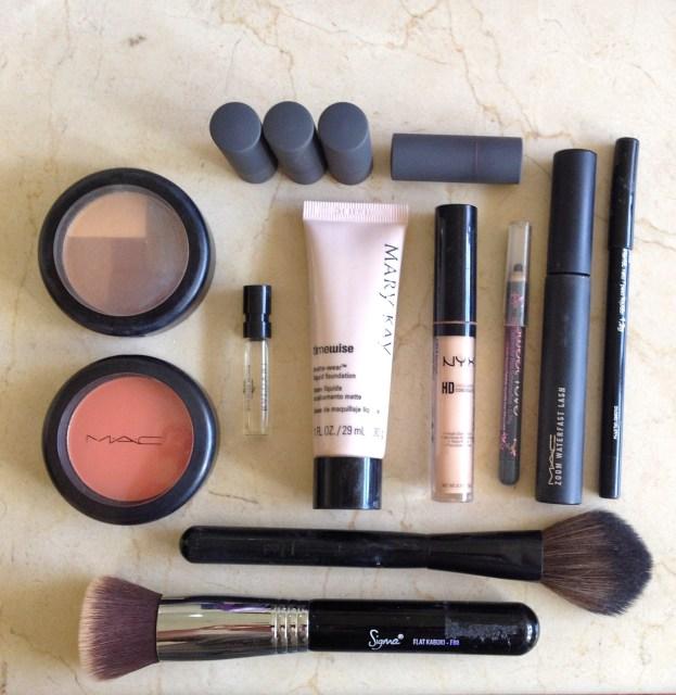 Os produtos acima são: batons, bronzer, blush, mini perfume, base, corretivo, lápis de olho, rímel e pinceis.