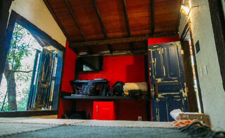 Foto do interior da suíte, com destaque para a TV e para o Frigobar