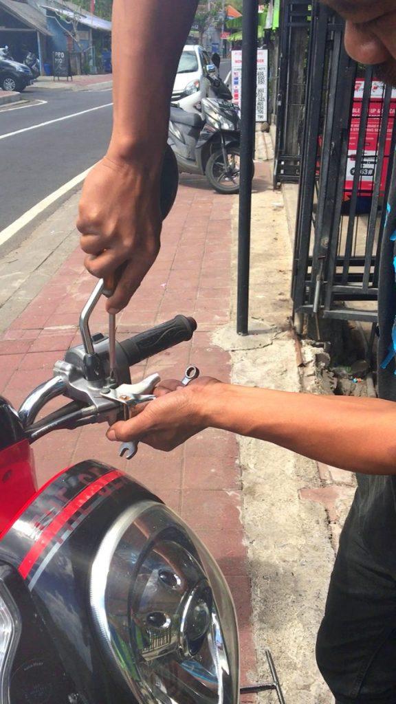 Mécanico indonesio arreglándonos el manillar de la moto