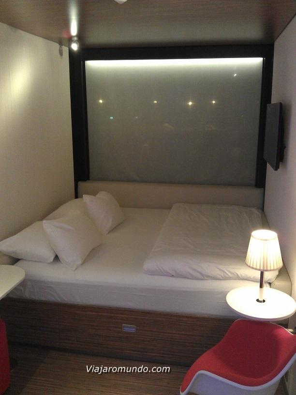 Cama, TV e janela com vista para a pista do aeroporto