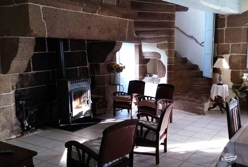Sala com lareira e escada de pedra ao fundo