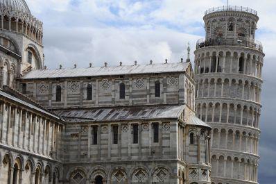 Vista de la torre de Pisa asomando inclinada tras la catedral