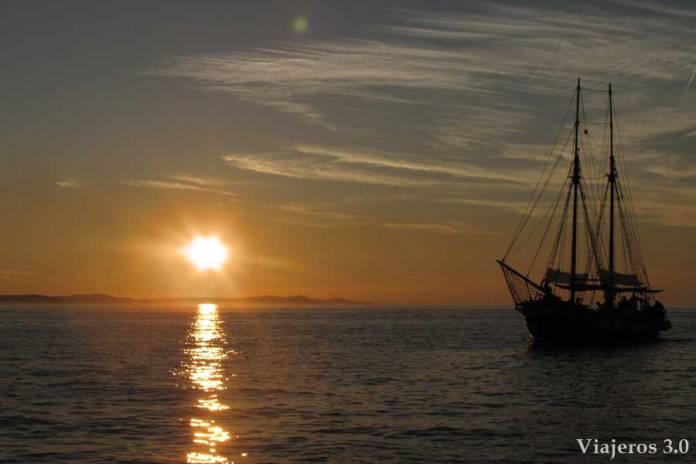 velero y puesta de sol desde el órgano del mar en Zadar