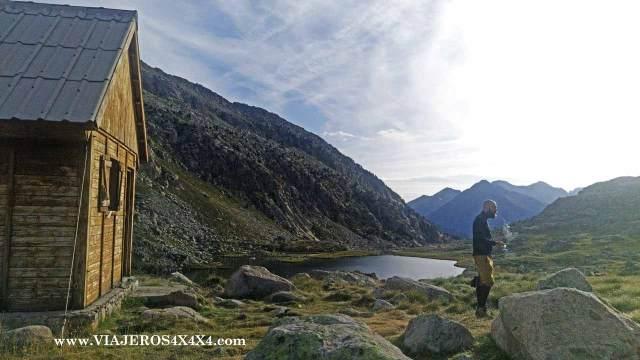 Refugio de montaña con un hombre observando la montaña