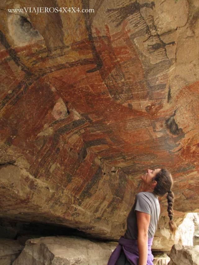 Pinturas rupestres en color rojo y negro sobre la cabeza de una mujer