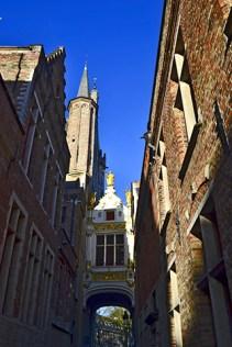 Callejuela arco pórtico dorado Vismarkt Brujas