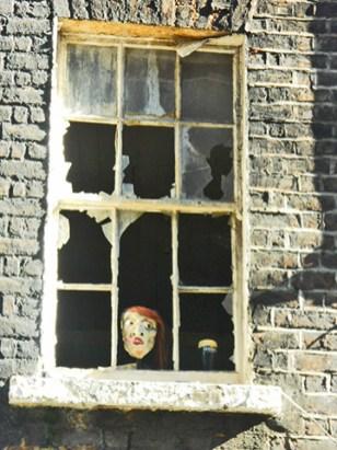 Rostro señora vigilando ventana rota edificio ladrillo afueras Dublín