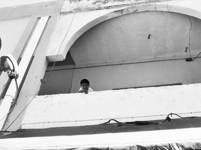 Niño sonrisa asomando balcón casa Essaouira blanco y negro