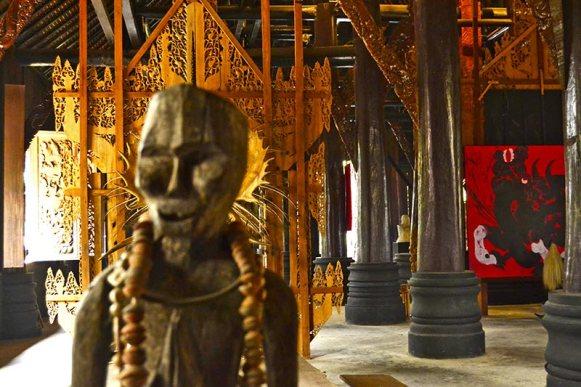 Estatua aborigen collar madera Casa Negra Chiang Rai