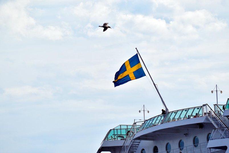 Gaviota volando bandera Suecia alto crucero archipiélago Estocolmo