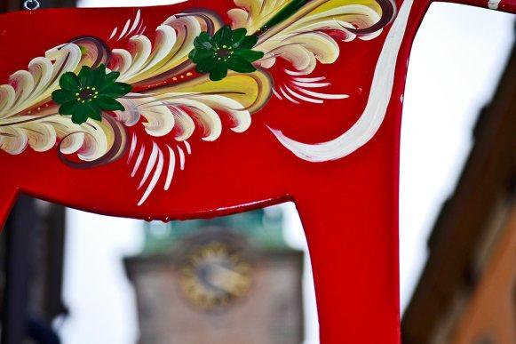 Letrero rojo caballo madera tienda Gamla Stan reloj torre catedral Storkyrkan Estocolmo