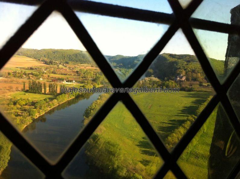 vista hacia el sur de la ribera del Dordogne, a través del entramado del vitral de una ventana
