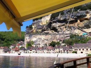 romántica vista general, desde la gabarra surcando el Dordogne: uniformes y ordenadas casas, flanqueadas por el fuerte troglodítico