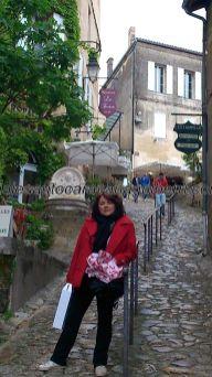 callejuela empinada típica, con restaurantes y terrazas dispuestos en escalones; cargando, gustosamente, con el vino comprado